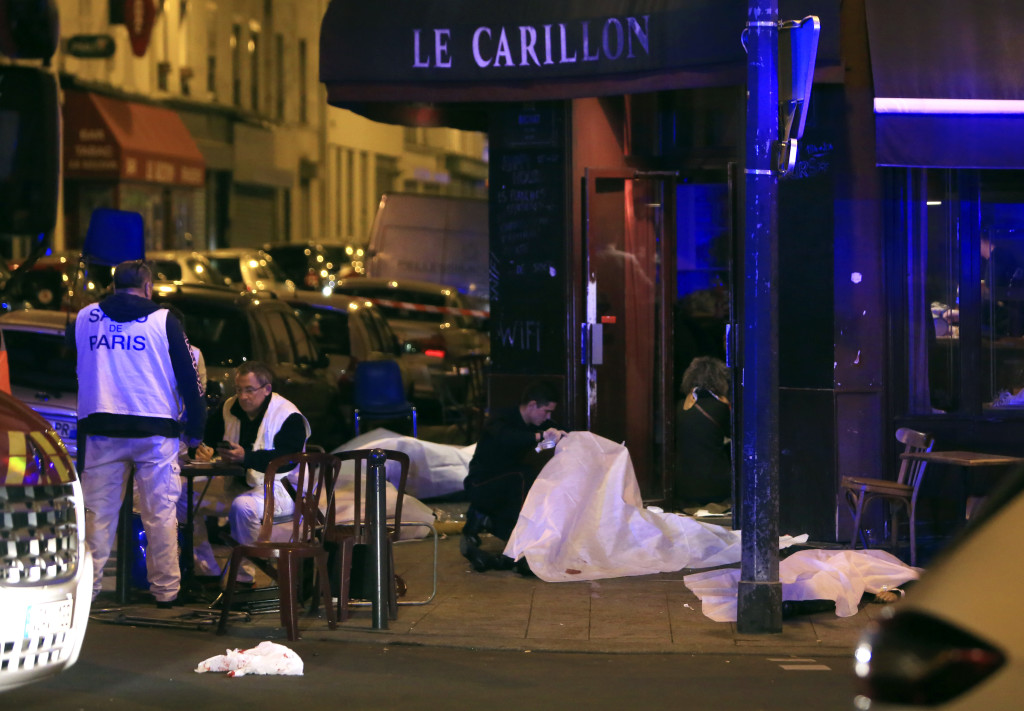 Victims lay on the pavement in a Paris restaurant, Friday, Nov. 13, 2015. Police officials in France on Friday reported a shootout in a Paris restaurant and an explosion in a bar near a Paris stadium. It was unclear if the events were linked. (AP Photo/Thibault Camus) NYTCREDIT: Thibault Camus/Associated Press